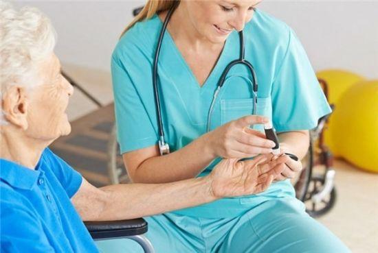Врач измеряет уровень сахара в крови у пациента